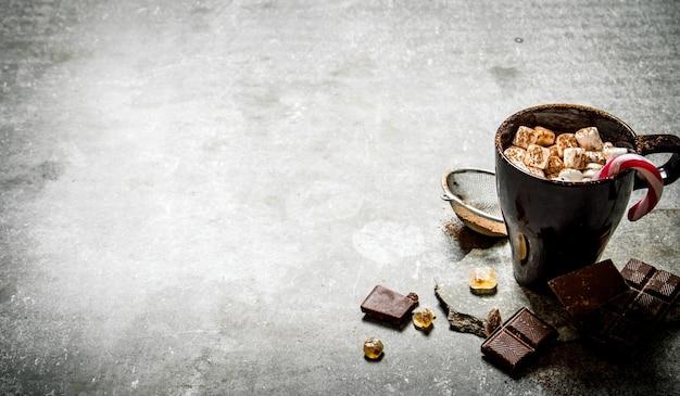 Heiße schokolade mit marshmallows und bitterschokolade. auf einem steinhintergrund
