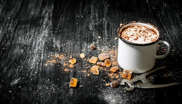 Heiße schokolade mit rohrzucker. auf schwarzem rustikalem tisch.