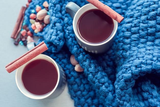 Heiße schokolade mit zimt und kandierten früchten über blau gestricktem plaid
