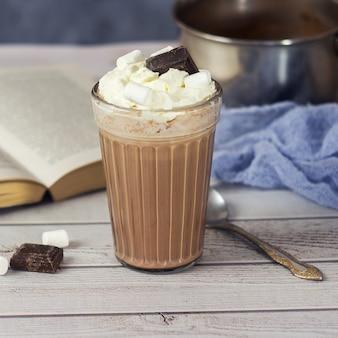 Heiße schokolade oder kakao im glas mit schlagsahne und schokoladenstücken