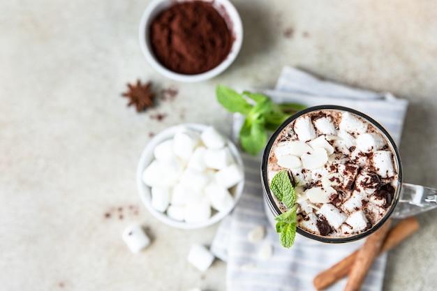 Heiße schokolade oder kakao im glasbecher mit marshmallow-zimt und minze