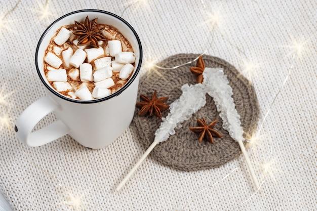 Heiße schokolade oder kakao mit eibischen in der weißen schale mit weihnachtslichtern