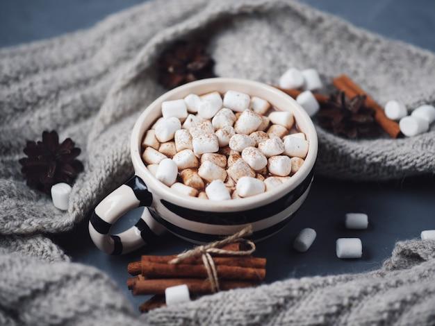 Heiße schokolade oder kakao mit marshmallows in einer zimtschale. warmer strickschal