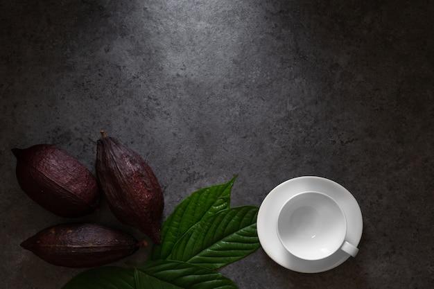 Heiße schokolade und kakaohülse schnitt kakaosamen auf dunkler tabelle, draufsicht mit kopienraum herausstellen