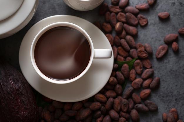 Heiße schokolade und kakaohülse schnitten das aussetzen von kakaosamen auf dunkler tabelle