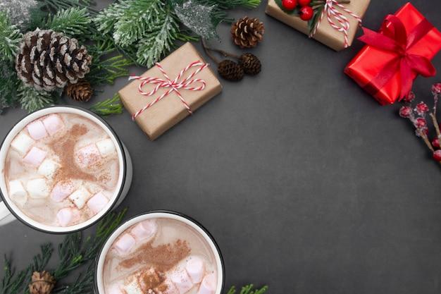 Heiße schokoladenbecher mit eibischen und weihnachtsgeschenkboxen. kopieren sie platz.