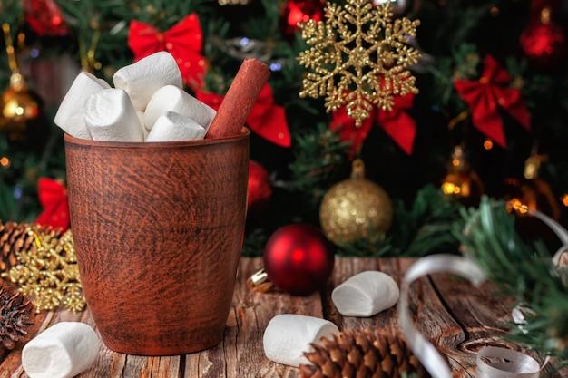 Heiße schokoladenbecher und marshmallows im hintergrund des weihnachtsbaumes