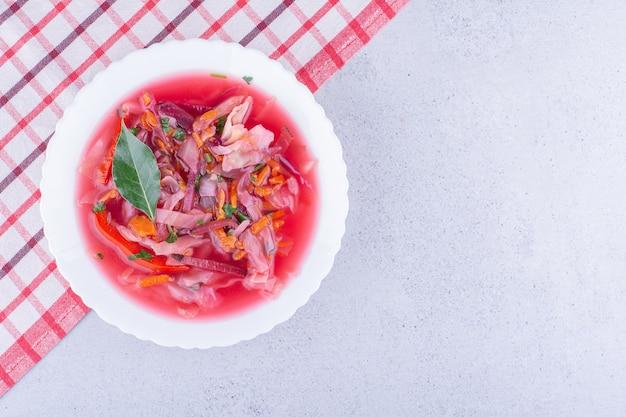 Heiße schüssel borschtschsuppe mit einem lorbeerblatt-topping auf einer tischdecke auf marmorhintergrund. foto in hoher qualität