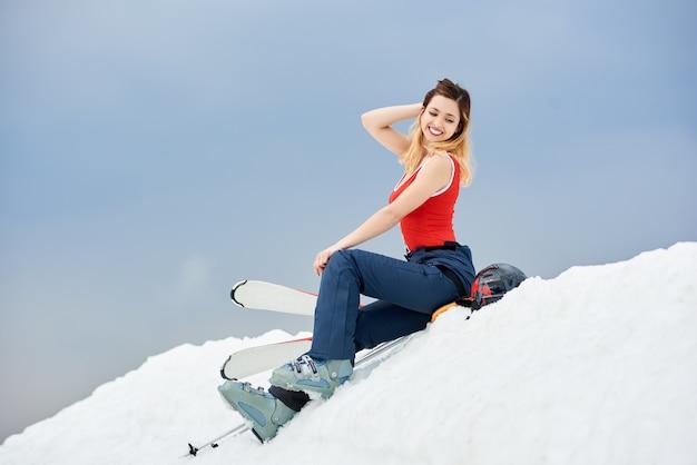 Heiße skifahrerin posiert auf der spitze des schneebedeckten hügels mit skiausrüstung am skigebiet.