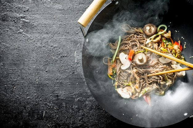 Heiße sobanudeln in einer wokpfanne mit pilzen, sauce und rindfleisch auf schwarzem holztisch