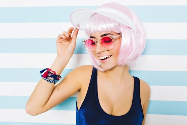 Heiße sommerstrandzeit des nahaufnahmeporträts der modischen frau in der rosa sonnenbrille, mit geschnittener rosa frisur, die spaß auf gestreifter wand hat. stilvoller sexy look, fröhliche stimmung, lächeln mit geschlossenen augen.