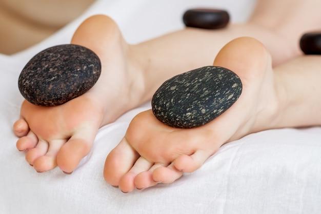 Heiße steine, die auf weiblichen füßen liegen