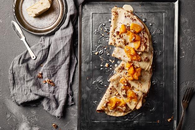 Heiße süße pfannkuchen mit pfirsich auf einem tablett