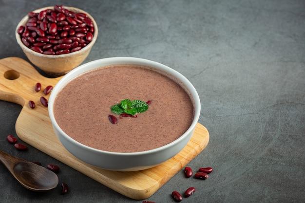 Heiße suppe der roten bohne in der weißen schüssel auf holzschneidebrett legen