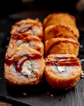 Heiße sushi-rollen mit sauce serviert