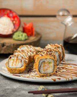 Heiße sushirollen mit garnelen und gurken, garniert mit soße und sesam