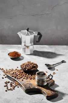 Heiße tasse espresso mit auf holzbrett verstreuten kaffeebohnen und einer kanne unter harter morgensonne