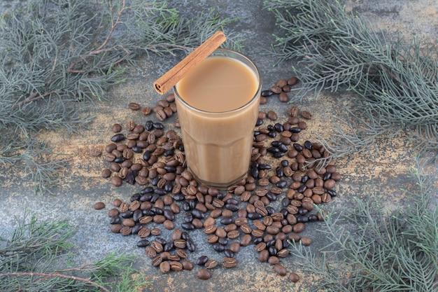 Heiße tasse kaffee mit zimtstange und kaffeebohnen auf marmorhintergrund. foto in hoher qualität