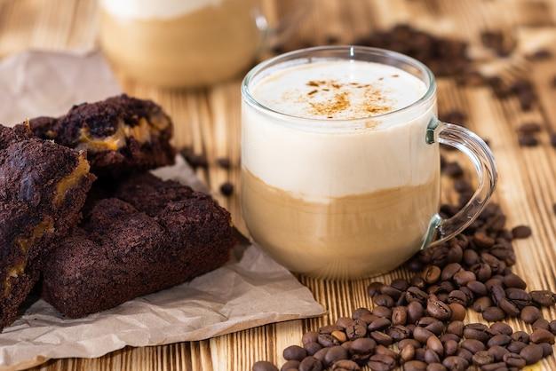 Heiße tasse latte und ein schokoladenmuffin auf holztisch.