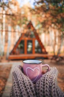 Heiße tasse tee, die frauenhände im wollpullover auf hintergrund des gemütlichen hauses am herbsttag wärmt
