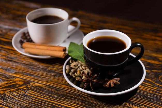 Heiße tasse tee im fokus mit kaffee dahinter