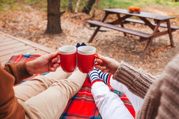Heiße tassen des tees in den händen im wollpullover auf hintergrund des gemütlichen hauses