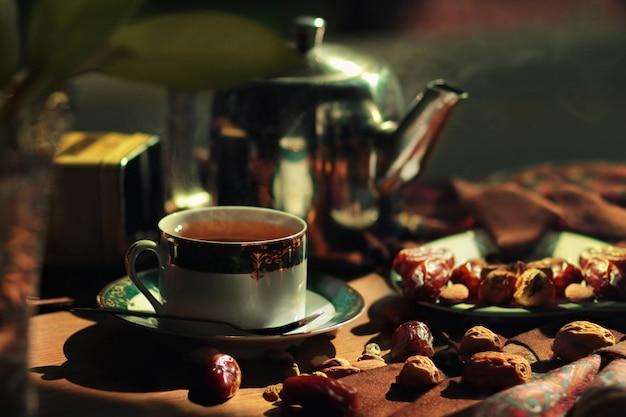 Heiße teekanne und tasse mit dattelfrüchten, nüssen und getrockneten früchten.