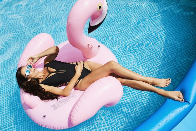 Heiße und modische brünette, fitness-model-frau mit perfektem sexy körper in stilvollem schwarzen bikini und glamouröser sonnenbrille, die sich auf einem aufblasbaren rosa flamingo bräunt und am pool posiert