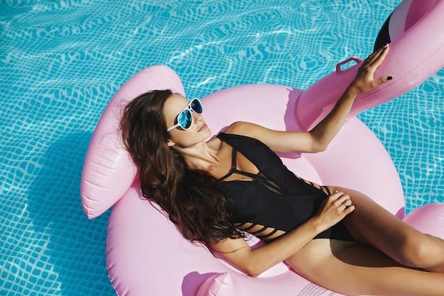 Heiße und modische brünette modelfrau mit perfektem sexy körper im stilvollen schwarzen bikini und glamouröser sonnenbrille, die sich auf dem schwebenden rosa flamingo bräunt, der am swimmingpool aufwirft
