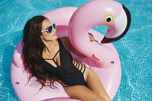 Heiße und modische brünette modelfrau mit perfektem sexy körper in stilvollem schwarzen bikini und glamouröser sonnenbrille, sitzt auf dem schwebenden rosa flamingo und posiert am pool