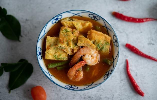 Heiße und saure suppe mit cha-om, ei und garnelen in einer weißen schüssel mit chili-kaffir-limettenblättern auf weißer oberfläche.