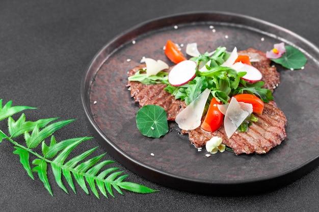 Heiße vorspeise dünne scheiben gegrilltes rindfleisch mit kirschtomaten, rucola