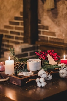 Heiße weihnachtsschokolade mit mini-marshmellows in einem alten keramikbecher mit kerzen auf einem holz.