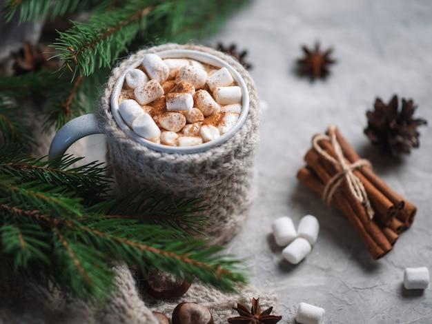 Heiße wintergetränkschokolade, -kakao oder -kaffee mit eibischen auf dem tisch in einer gestrickten tasse mit zimt