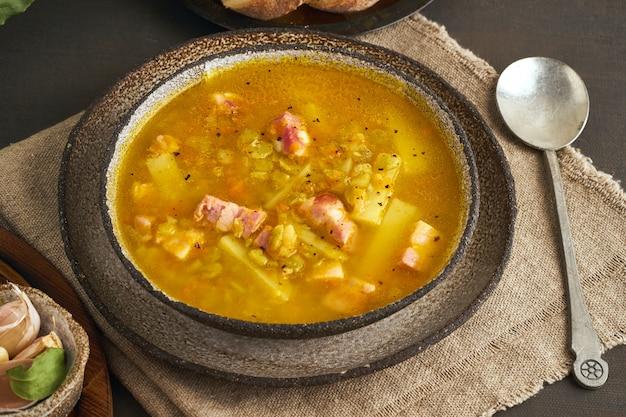 Heiße wintersuppe mit gehackten grünen erbsen, schweinefleisch, speck, geräuchert auf dunkelbraunem holztisch