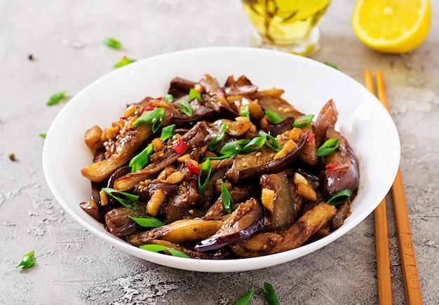 Heiße würzige eintopfaubergine im koreanischen stil mit frühlingszwiebel. aubergine sautieren.