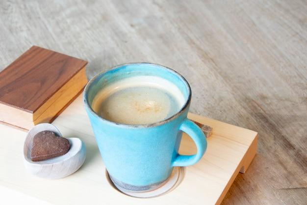 Heißer cappuccino in der tasse auf holztisch