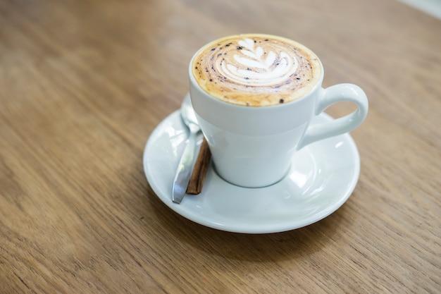Heißer cappuccinokaffee mit weißer schale auf holztisch