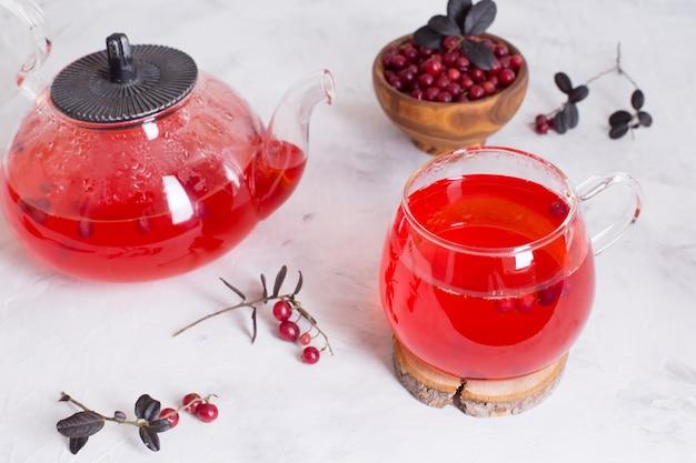 Heißer cranberry-tee in einer glasschale und einer teekanne auf einem hellen hintergrund.