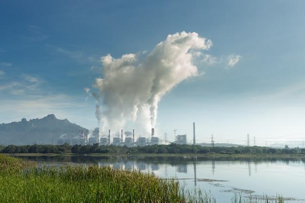 Heißer dampf von den kaminkohlekraftwerken gegen blauen himmel.