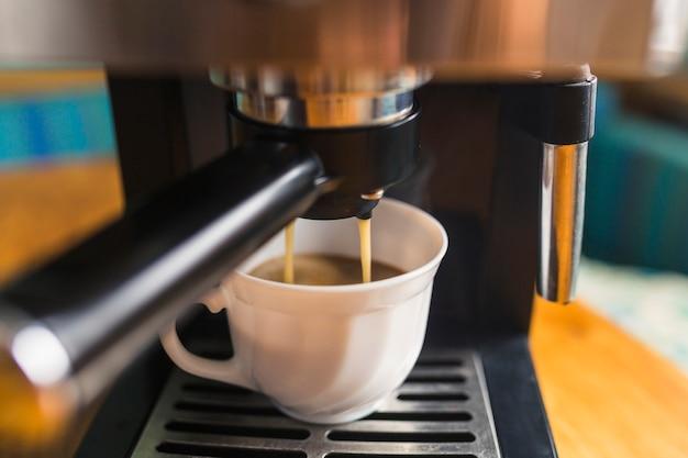 Heißer espresso, der in porzellanbecher gießt