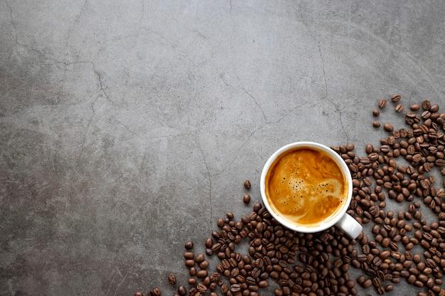 Heißer espresso und kaffeebohnen auf altem zementbodenhintergrund