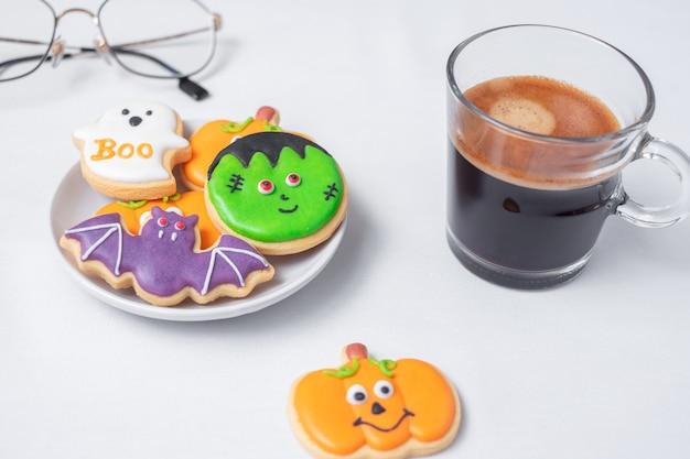 Heißer espressokaffee oder schokoladentasse mit lustigen halloween-plätzchen. fröhlicher halloween-tag, trick oder bedrohung, hallo oktober, herbstherbst, traditions-, party- und urlaubskonzept