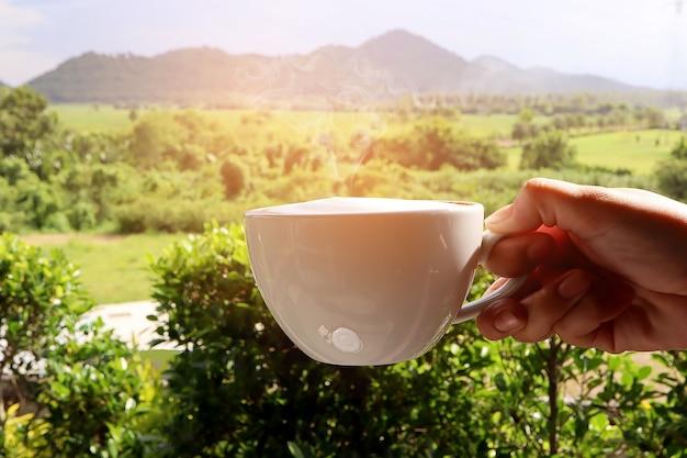 Heißer frischer kaffee latte in einer schale in der hand mit milchschaum, rauch