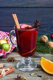 Heißer glühwein im glasbecher auf einem holztisch. duftendes traditionelles wintergetränk basierend auf wein, saft, gewürzen, gewürzen, früchten. nahansicht
