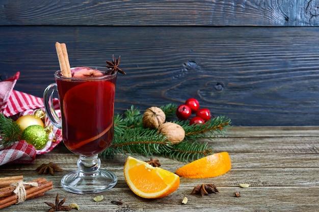 Heißer glühwein im glasbecher auf einem holztisch. duftendes traditionelles wintergetränk basierend auf wein, saft, gewürzen, gewürzen, früchten.