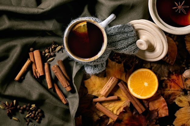 Heißer glühwein im keramiktopf und becher im schal mit gewürzen, orange und herbstlaub über dunkler leinentischdecke. flach liegen. gemütliche warme atmosphäre. flach legen
