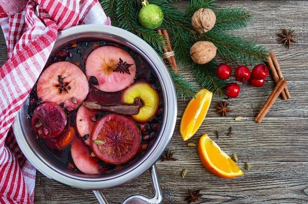 Heißer glühwein in einer großen pfanne auf einem holztisch. duftendes traditionelles wintergetränk basierend auf wein, saft, gewürzen, gewürzen, früchten. draufsicht.