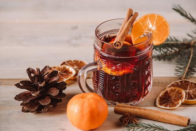 Heißer glühwein mit früchten und gewürzen auf holzuntergrund winterwärmendes getränk für den urlaub