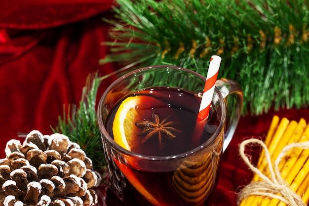 Heißer glühwein mit gewürzen auf weihnachtshintergrund